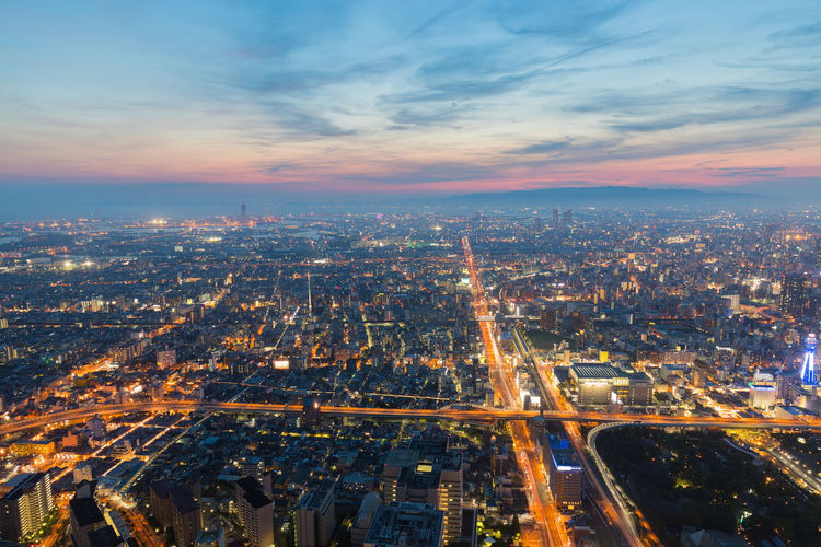 High angle view of illuminated city against sky during sunset