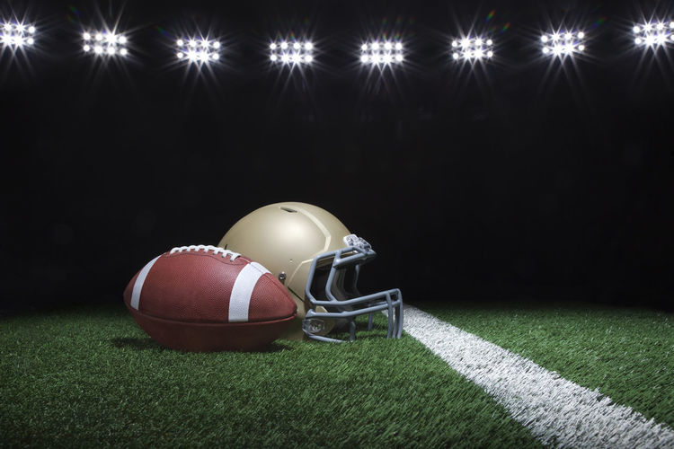 Football and helmet on field under lights at night American Dramatic Lighting Football Gold Leather Lights Low Angle View Modern Objects Stadium Stripes Ball Black Contrast Dark Background Facemask Flare Of Light Helmet Night No People Shadow Sport Spot Lighting Team Sport Turf