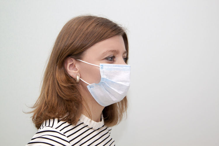 Young woman with protective face mask against white back ground