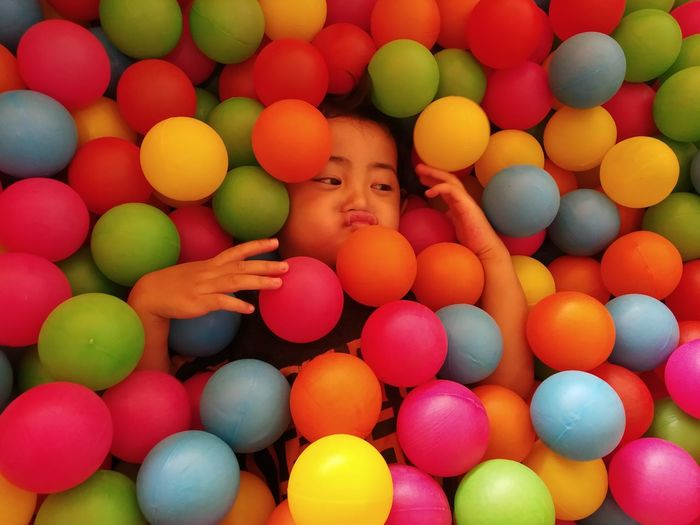 High angle view of girl amidst multi colored balls
