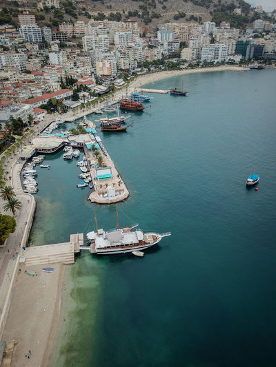 High angle view of sailboats moored on sea by buildings in city