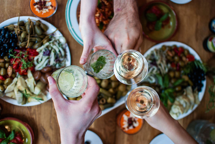 Cropped image of friends toasting drinks over food on table