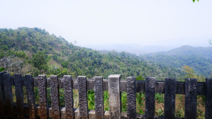Panoramic view of wooden fence on mountain against sky