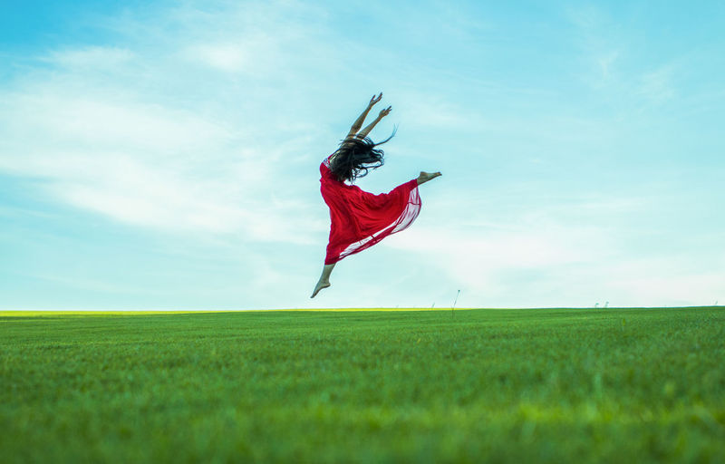 Side view of woman dancing on grassy field against sky