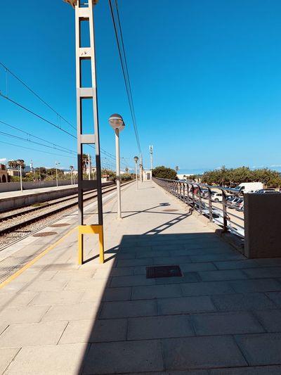 View of railroad station platform against blue sky