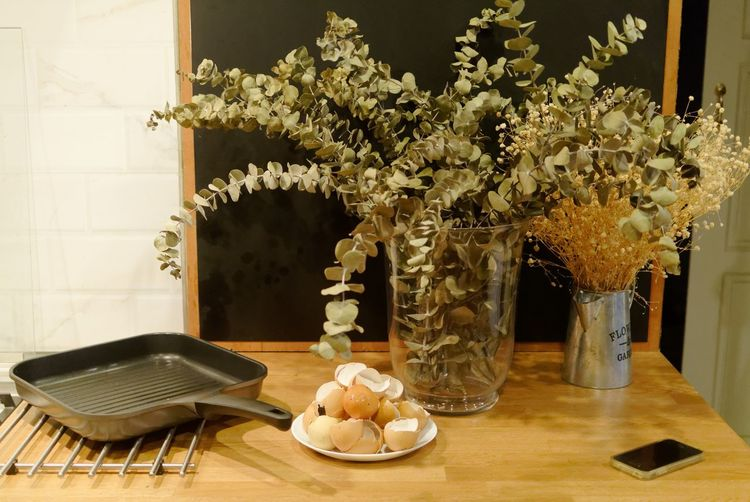 Eggshells And Frying Pan With Mobile Phone By Vases On Table