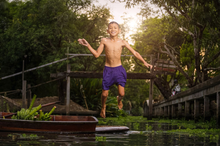 Full length of shirtless boy jumping in river