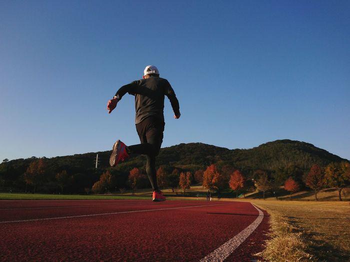 Full length of man running against clear blue sky
