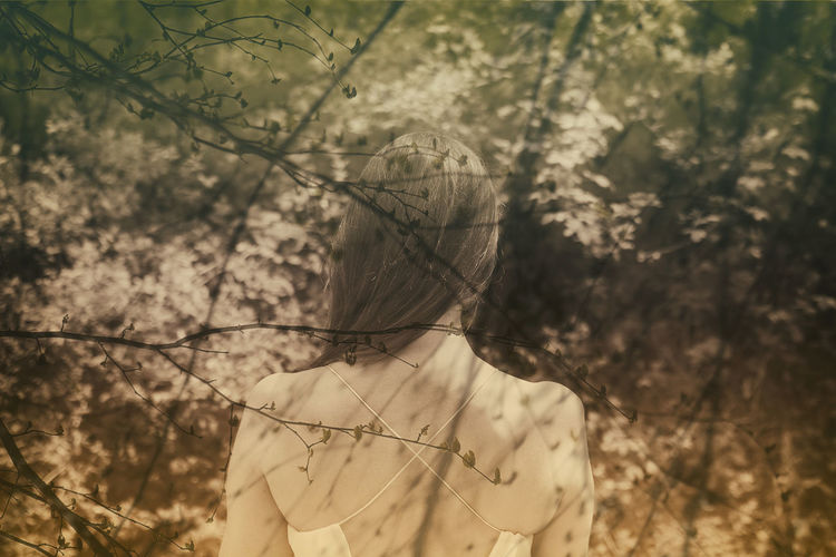 Digital composite image of woman standing by tree