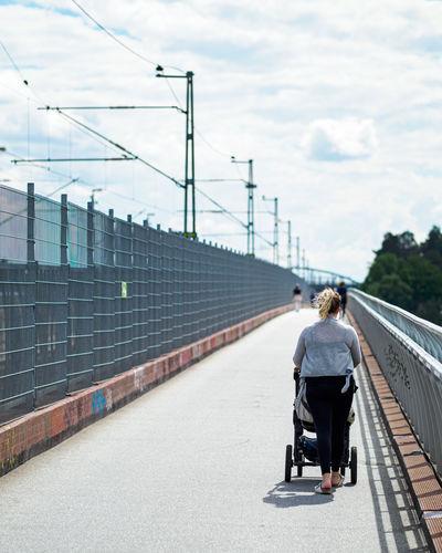 Rear view of woman walking on bridge against sky