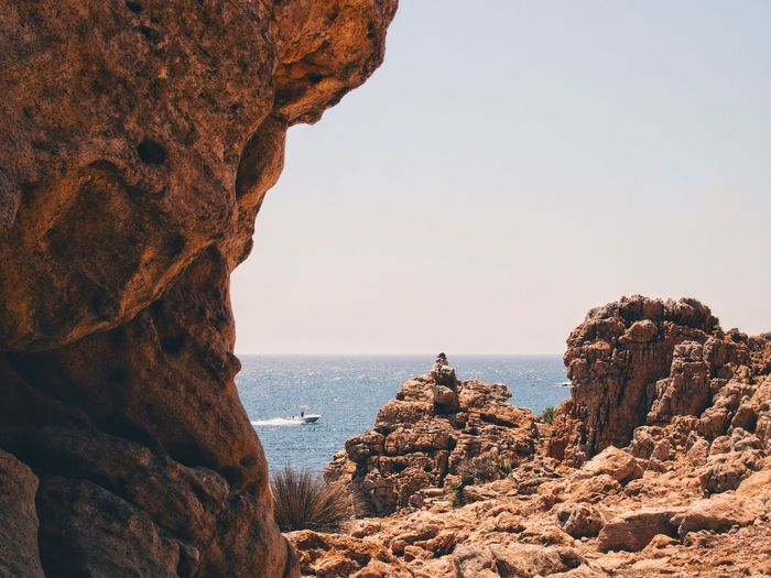 Scenic view of sea against clear sky from rocky shore