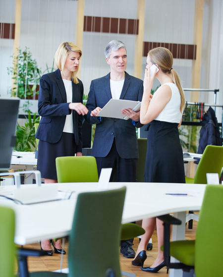 Business People Discussing Over Document While Standing In Office