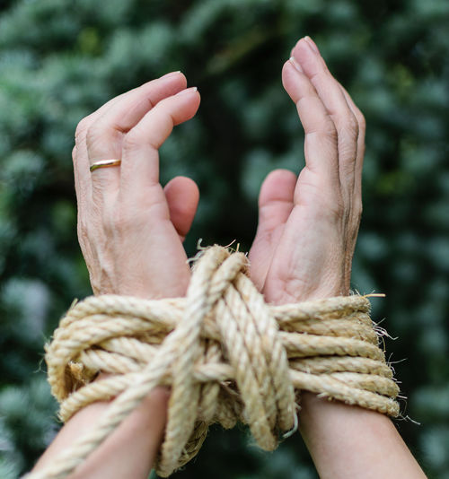 Cropped hands of person tied with rope