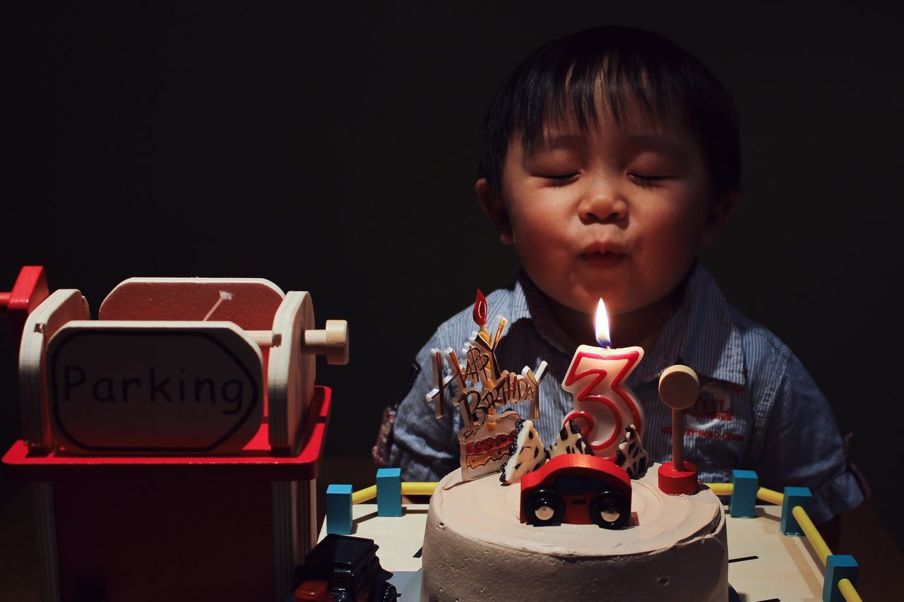 Cute boy with eye closed blowing birthday candle on cake in darkroom