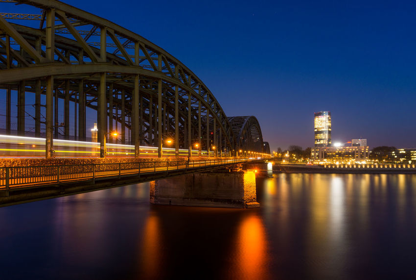View of the illuminated Hohenzollerbridge, a passing Train, the Cologne Triangle, the Hyatt Hotel and the River Rhine in Germany Cologne 2018. Architecture Built Structure Illuminated Building Exterior Reflection City Sky Water Night Bridge Connection Bridge - Man Made Structure Dusk River No People Travel Destinations Skyscraper Outdoors Office Building Exterior Building Waterfront Nature Germany Cologne Hohenzollernbridge