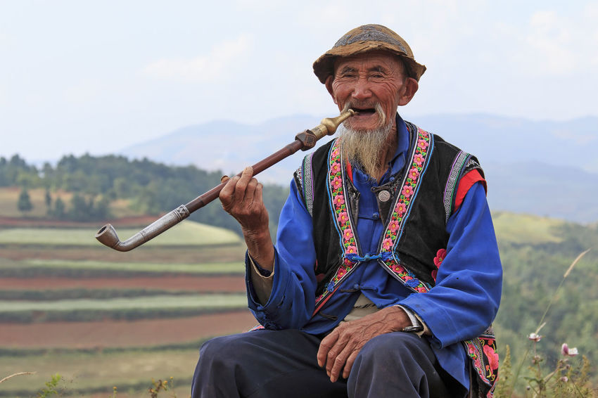 Dongchuan, China - September 27, 2016: An old chinese man dressed with the traditional attire smoking while enjoying the panorama of DongChuan in Yunnan Province, China ASIA Casual Clothing China Chinese Minority Cloud Cropped Dongchuan Enjoyment Field Focus On Foreground Front View Hill Holding Leisure Activity Lifestyles Looking At Camera Man Red Land Sitting Sky Smoking South East Asia Terraces Three Quarter Length Traditional