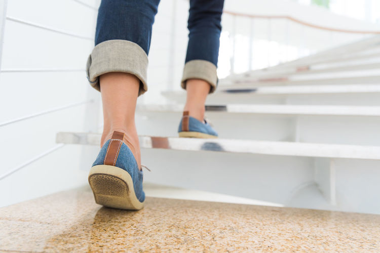 Young adult woman walking up the stairs with sun sport background. Achievement Blocks Briefcase Business Career Climb Concept Goal Job Ladder Office People Progress Runner Shoes Stairs Staircase Stairway Step Stepping Success Walking Successful Woman Background