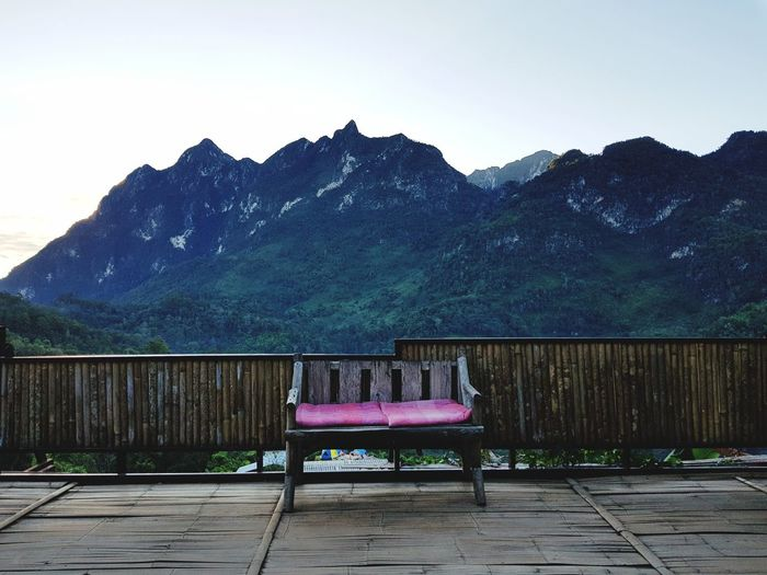Empty Bench On Porch With Mountains In Background