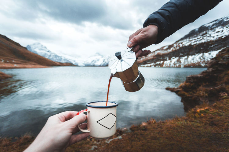 Cropped hand holding coffee cup while person pouring drink against sea