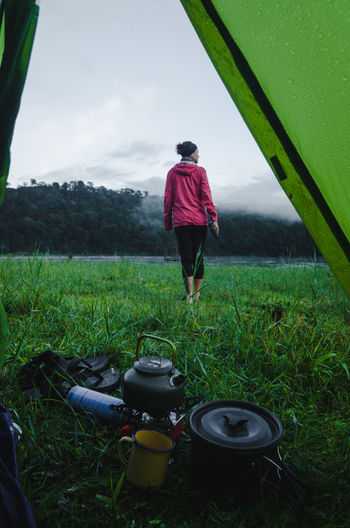 Rear view of woman walking on grass seen though tent in forest