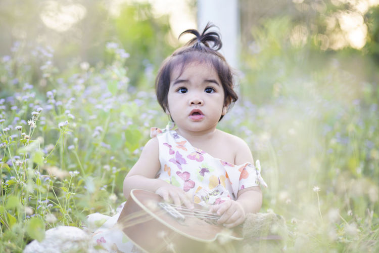 Portrait of cute baby girl sitting on plant