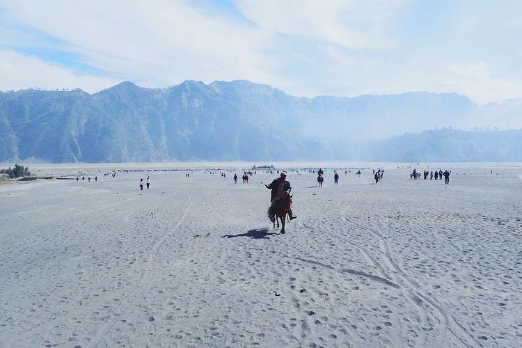 Man riding horse on sand in desert against sky