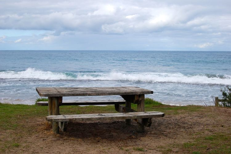 Chairs and table on beach against sky