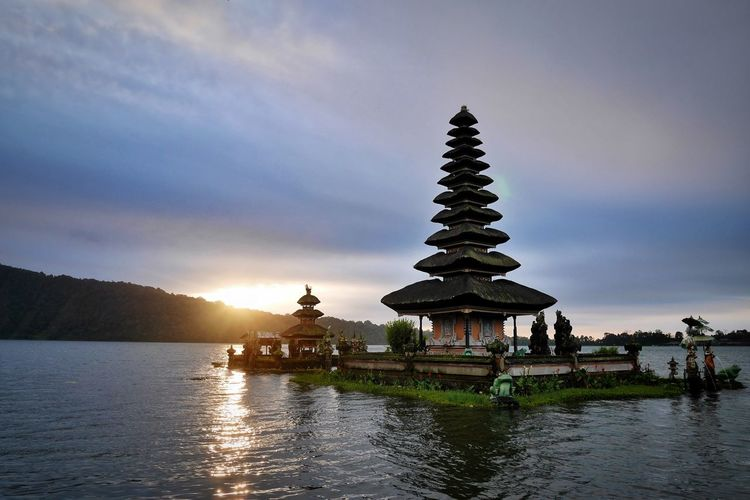 Traditional building by lake against sky during sunset