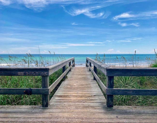 Empty wooden walkway leading towards sea against sky
