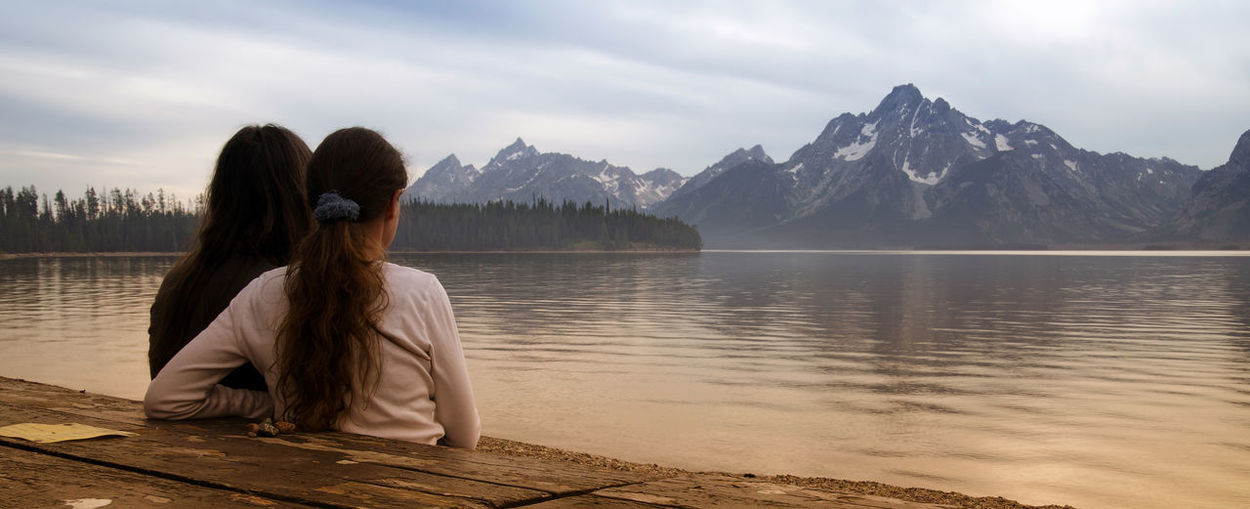 Rear View Of Female Friends Looking At Lake Against Mountains During Winter