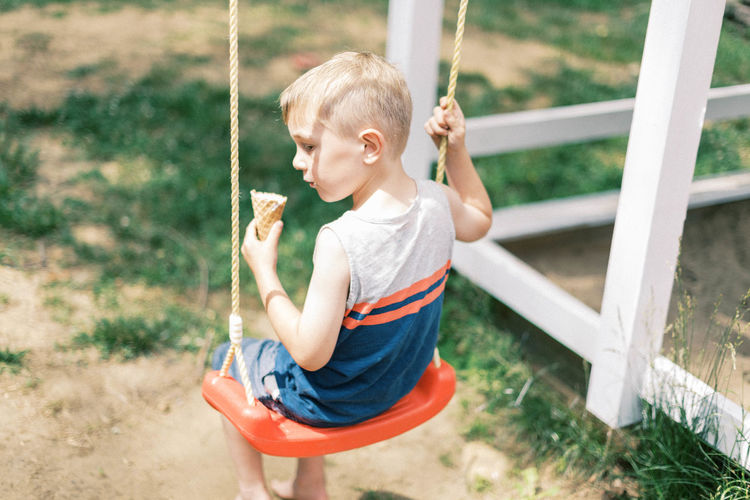 Full length of boy playing on swing at playground