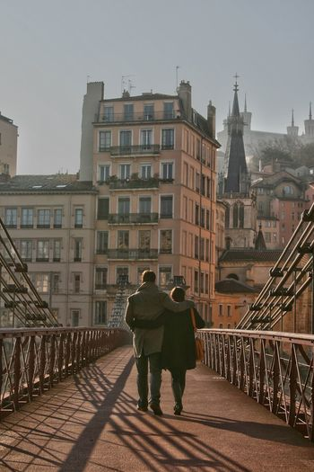 Rear view of couple on footbridge against buildings