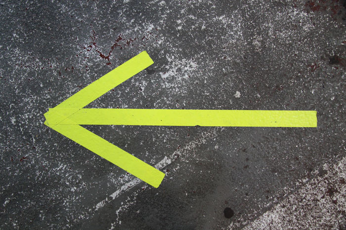 Arrow Arrow Sign Arrow Symbol Asphalt Backgrounds City Close-up Communication Day Direction Gray Guidance Marking No People Outdoors Road Road Marking Sign Symbol Warning Sign Yellow