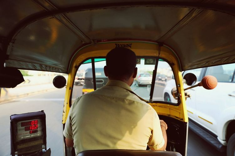 Rear view of driver driving rickshaw
