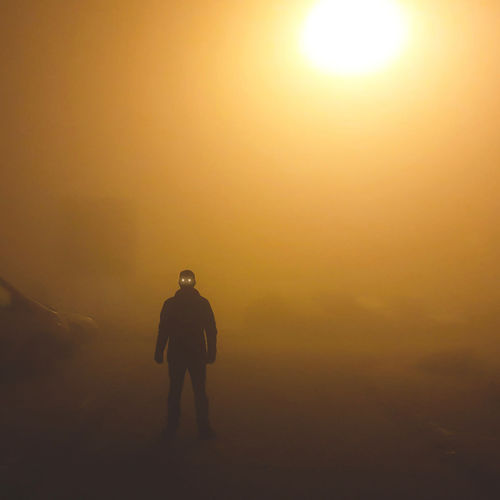 Silhouette man standing on street in strong fog night
