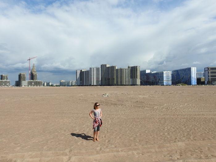 Full length of woman on beach against sky in city