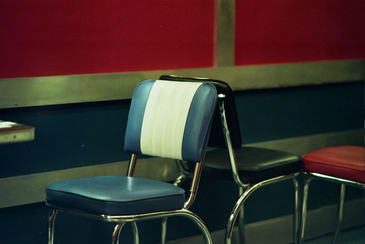Close-up of empty chairs and table by wall
