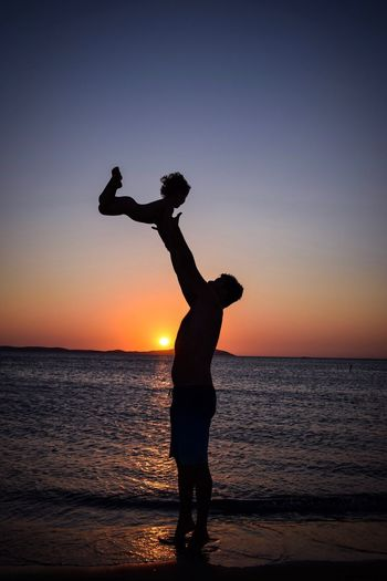 Silhouette Father Tossing Child At Beach Against Clear Sky During Sunset