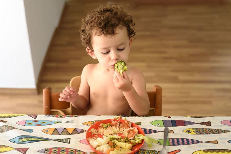 Happy boy sitting on table