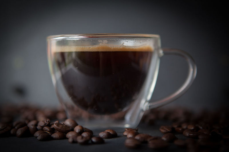 Coffee cup with fresh brewed coffee and brown roasted coffee beans scattered on black stone background side view Food And Drink Drink Coffee Refreshment Roasted Coffee Bean Coffee - Drink Cup Mug Indoors  No People Studio Shot Food Close-up Still Life Heat - Temperature Freshness Table Coffee Cup Glass Hot Drink Dark Latte Caffeine