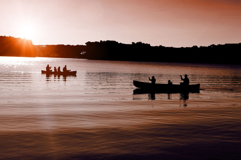 Late evening canoers Beauty In Nature Day Lake Leisure Activity Lifestyles Men Nature Nautical Vessel Outdoors Paddleboarding People Real People Reflection Scenics Silhouette Sitting Sky Sunset Togetherness Tranquil Scene Tranquility Tree Vacations Water Waterfront