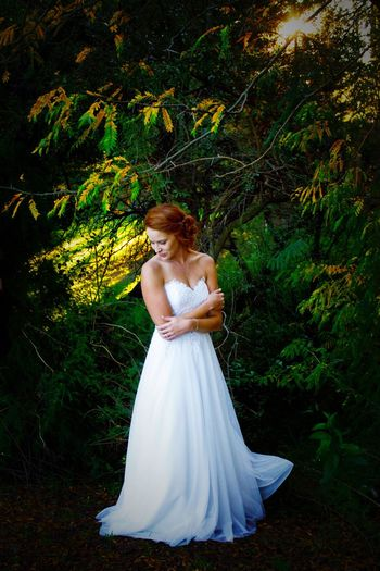 Bride Standing In Wedding Dress Against Trees