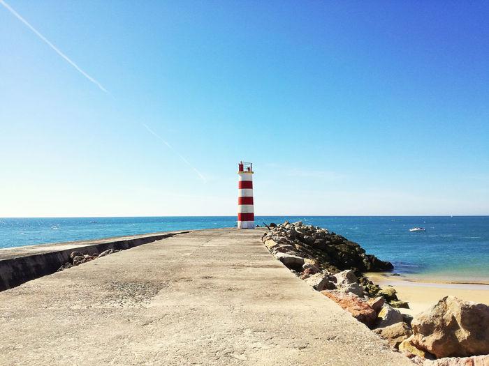 Lighthouse On Beach Against Clear Blue Sky