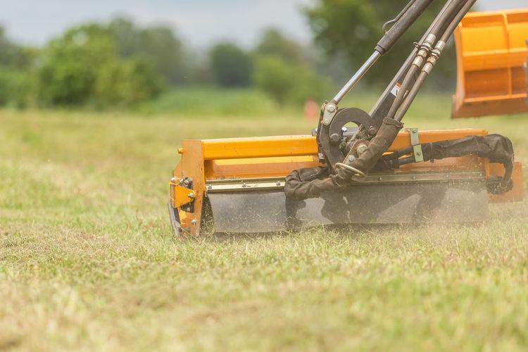 Close-up of yellow machinery on field