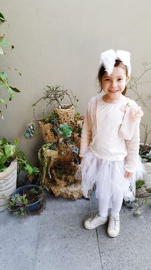 Full Length Of Girl Standing By Potted Plants