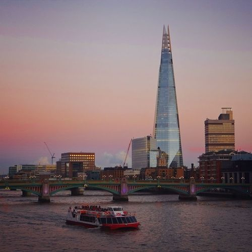 Shard London Bridge By Thames River Against Sky During Sunset In City