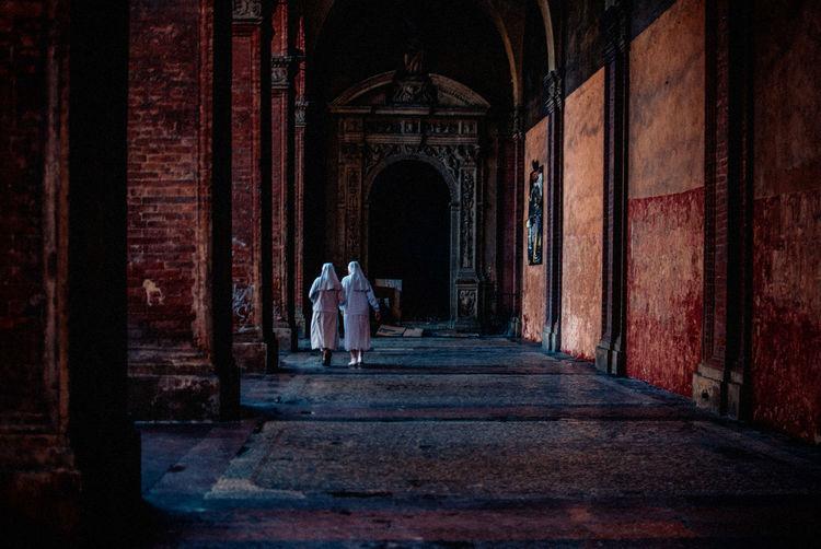 Rear View Of Women Walking In Archway