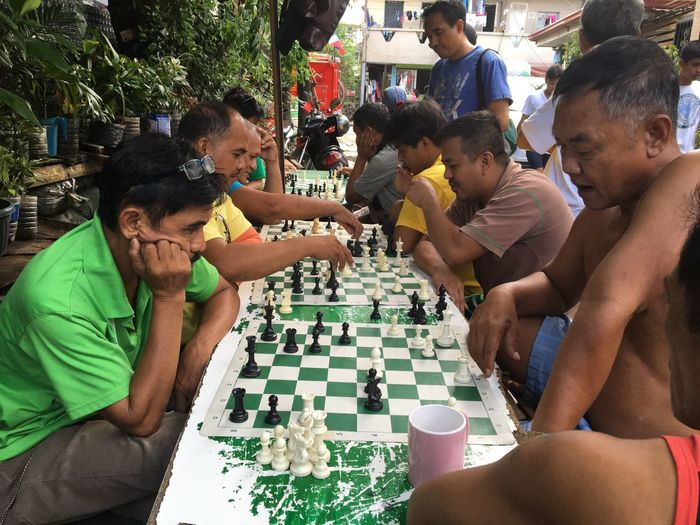 People play chess at a side street in Taguig city in metropolitan Manila. Leisure Activity Sitting Lifestyles Cultures Men Casual Clothing Outdoors Togetherness Chess Chessgame Chessboard Sports Life  Philippines Taguig Village Life