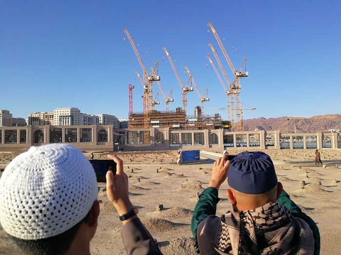 Jannat al-Baqīʿ is a cemetery in Medina Cemetery Graveyard Al Baqi Sand Real People Sky Built Structure Architecture Clear Sky Building Exterior Nature Crane - Construction Machinery Day People Lifestyles Sunlight Leisure Activity Men Rear View Hat Group Of People Machinery Blue City Outdoors