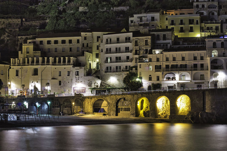 Arch bridge over river by buildings in city at night